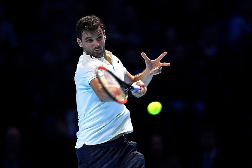 Grigor Dimitrov of Bulgaria hits a forehand during his 6-3, 5-7, 7-5 ATP Tour Finals victory over Dominic Thiem of Austria yesterday. He squandered two match points when serving for the match but clinched the third.