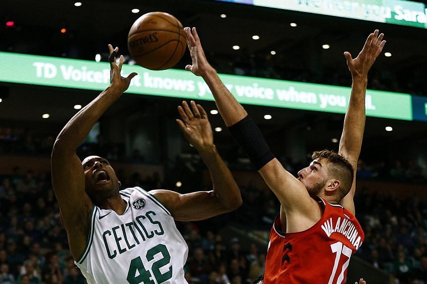 Boston Celtics forward Al Horford is blocked by Toronto Raptors centre Jonas Valanciunas - illegally, according to the referee - during their game at the Boston Garden. Horford led his team in points, as the Celtics made light of Kyrie Irving's absen