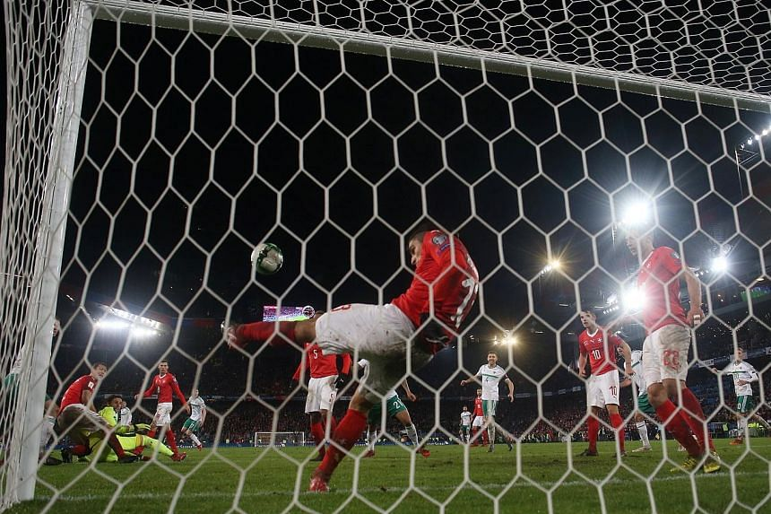 Left: Switzerland's players in a huddle after the final whistle to celebrate reaching next year's World Cup in Russia, having defeated Northern Ireland 1-0 on aggregate. Below: Switzerland's Ricardo Rodriguez clearing Jonny Evans' goal-bound header o