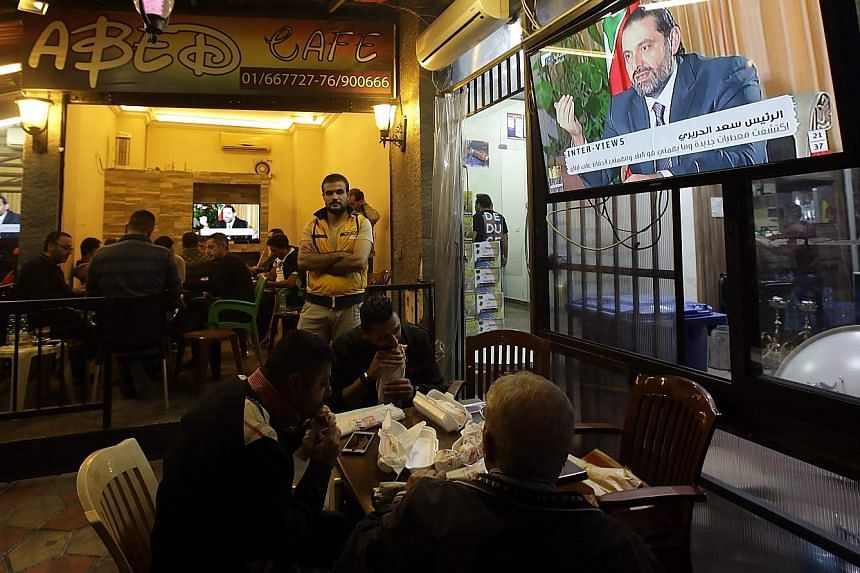 The interview with former Lebanese prime minister Saad al-Hariri with his party's Future TV channel being shown on a TV in a Lebanese cafe. The interview marks his first public comments since his surprise Nov 4 resignation.