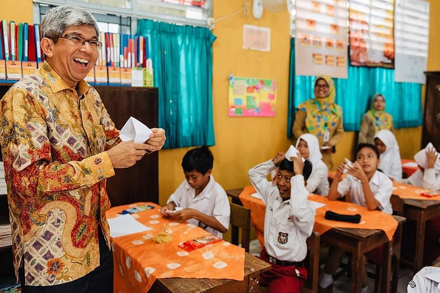 Dr Yaacob Ibrahim taking part in origami storytelling at one of the Yogyakarta schools in the Words on Wheels initiative.