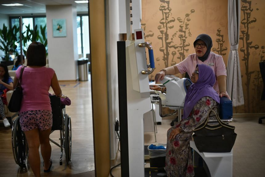 A woman uses one of the four kiosks that allow patients with chronic conditions to check their blood pressure or body mass index (BMI) at Bedok Polyclinic.