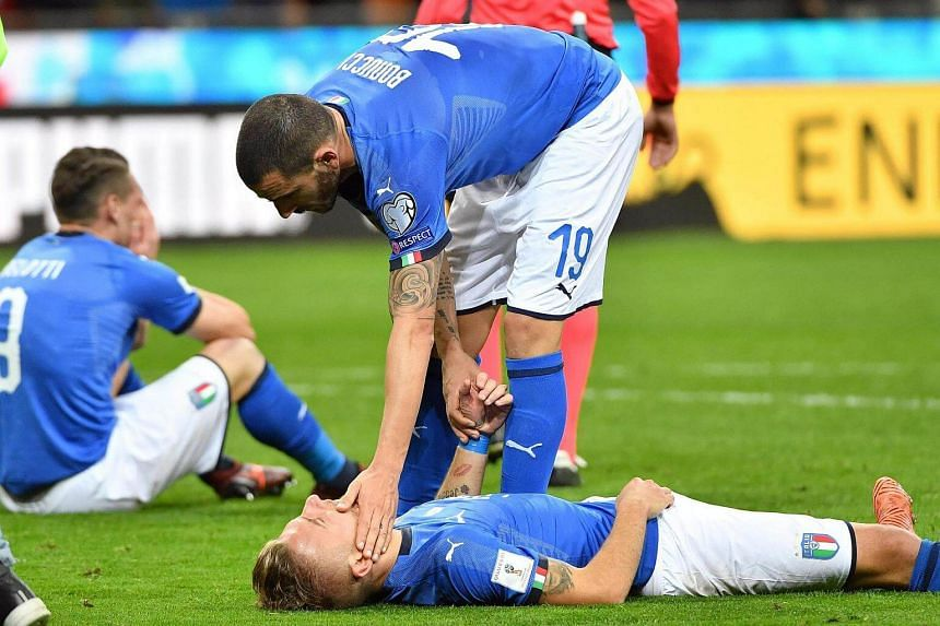 Italy's defender Leonardo Bonucci and teammate forward Ciro Immobile show their dejection at the end of the match.