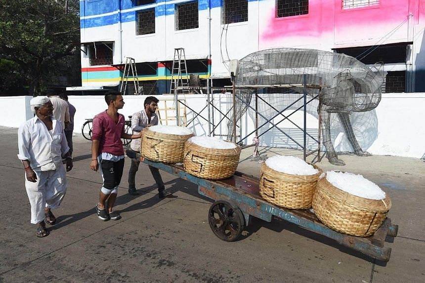 Indian fishermen pushing their catch past the main venue of the St+art Festival at Sassoon Dock.