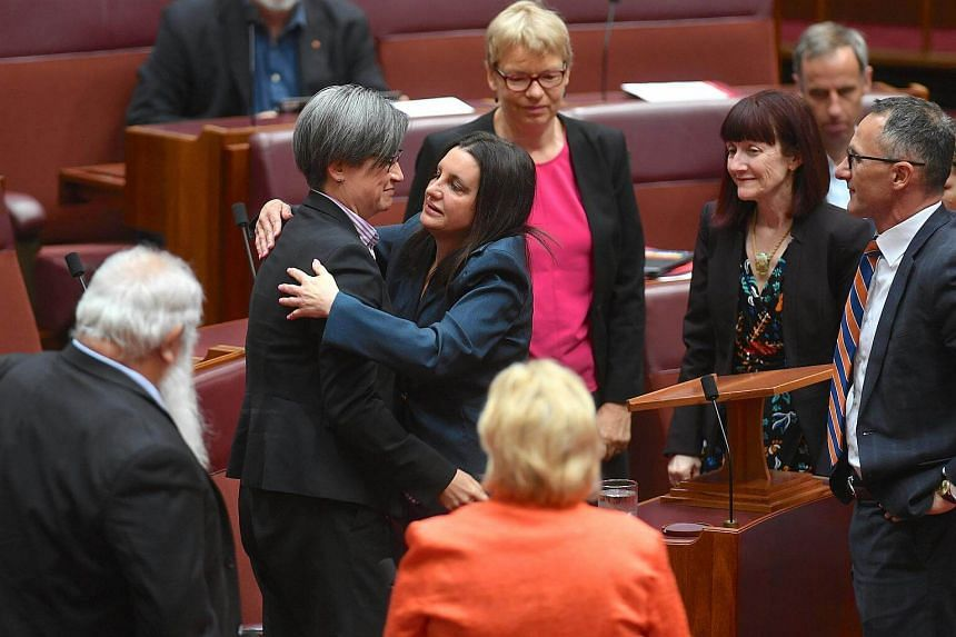 Jacqui Lambie, an independent and outspoken senator for the island state of Tasmania, is hugged by other senators after delivering a statement regarding her resignation.