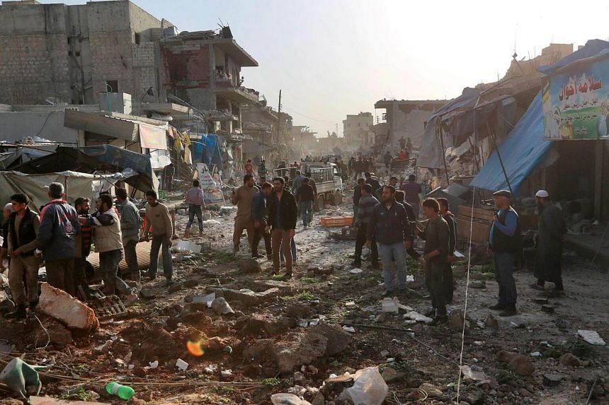 Syrians dig through the debris of a building as they search for survivors following a reported airstrike on the rebel-held town of Atareb.