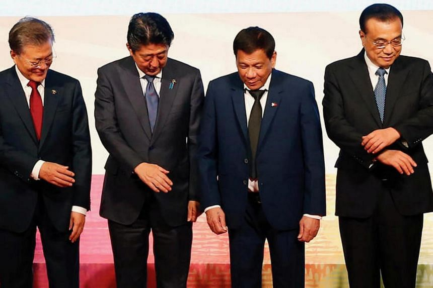 """A trilateral summit involving Japanese Prime Minister Shinzo Abe (second from left), Chinese Premier Li Keqiang (right) and South Korean President Moon Jae In (left) will be hosted by Japan at the """"earliest possible time""""."""