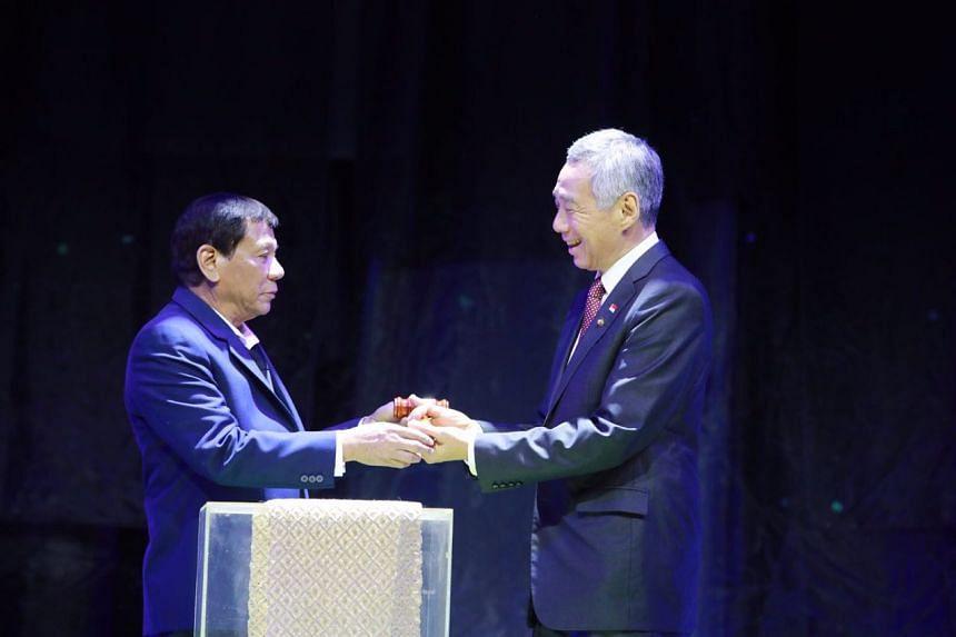 Prime Minister Lee Hsien Loong receiving the ceremonial gavel from Philippine President Rodrigo Duterte to symbolise the passing of Asean leadership, in Manila on Nov 14, 2017.