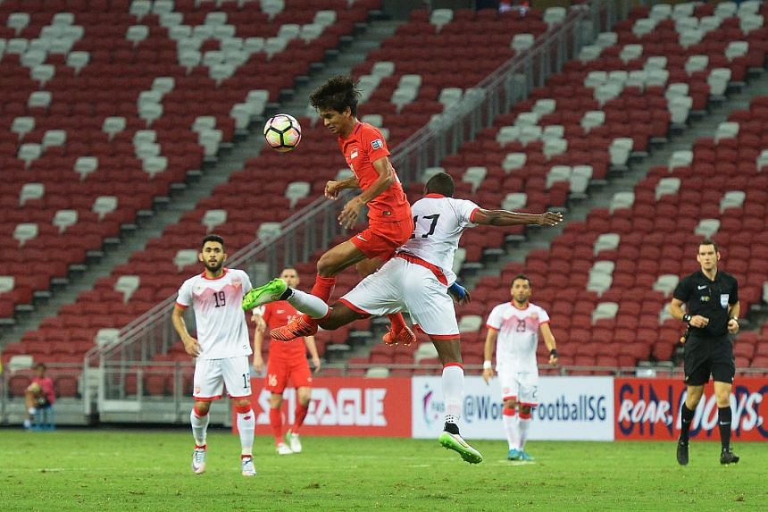 Singapore's Safuwan Baharudin (left) tussling for the ball with Bahrain's Abubaker Aadem during their Asian Cup qualifier at the National Stadium on Nov 14, 2017.