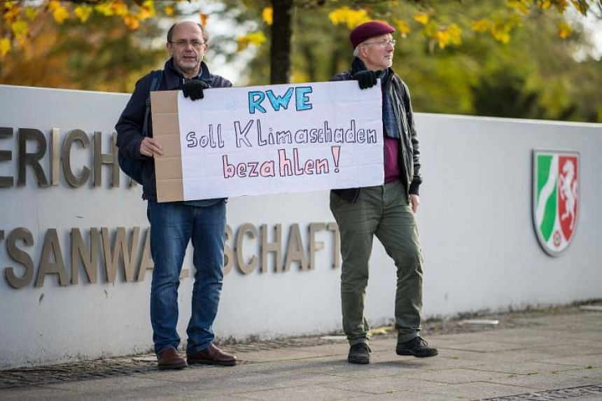 "Rolf Schwermer and Reinhard Suehling from the environmentalist organisation ""Fossil Free"" hold up a poster reading ""RWE should pay for climate damages"" in front of the higher regional court of Hamm, western Germany, where the hearing of an appeal beg"