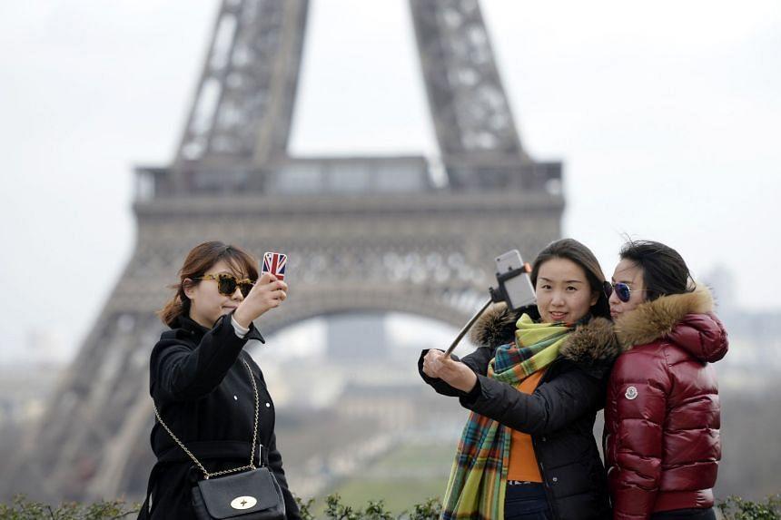 Tourists taking selfie's near the Eiffel Tower in Paris.