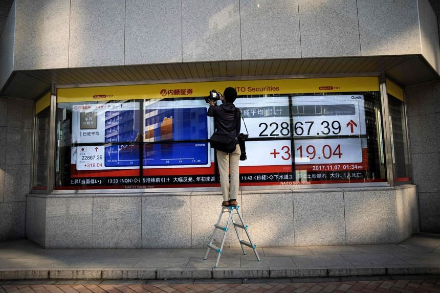 A photographer takes pictures of an electronics stocks indicator displaying share prices of the Tokyo Stock Exchange.