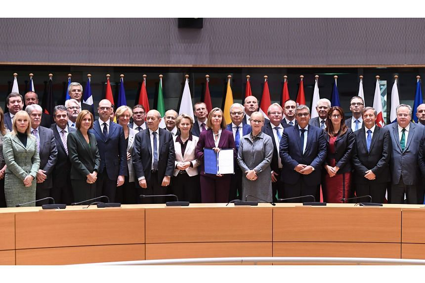 EU diplomatic chief Federica Mogherini (centre) with some foreign and defence ministers from 23 member states after the Pesco signing yesterday in Brussels.