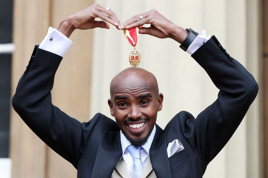 Britain's Mo Farah does his trademark Mobot as he poses with his medal after being knighted.