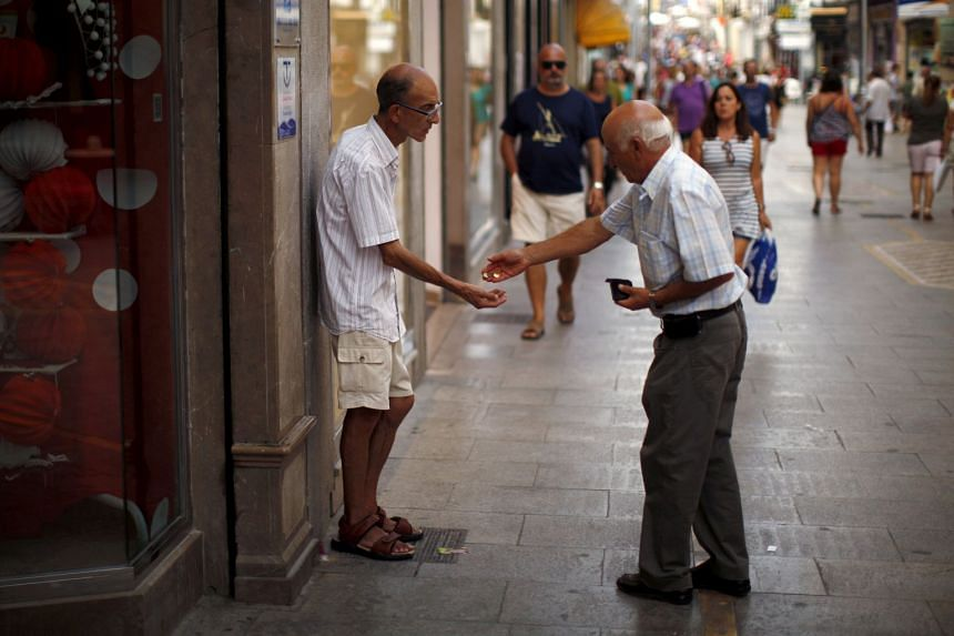 A man gives coins to a beggar in downtown Ronda, southern Spain, in a 2015 file photo.