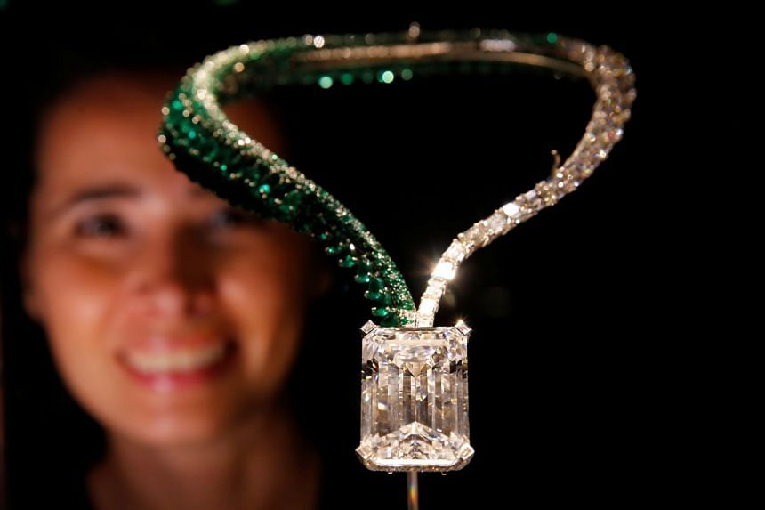 A Christie's staff member poses behind The Art of de Grisogono necklace featuring the 163.41-carat diamond.