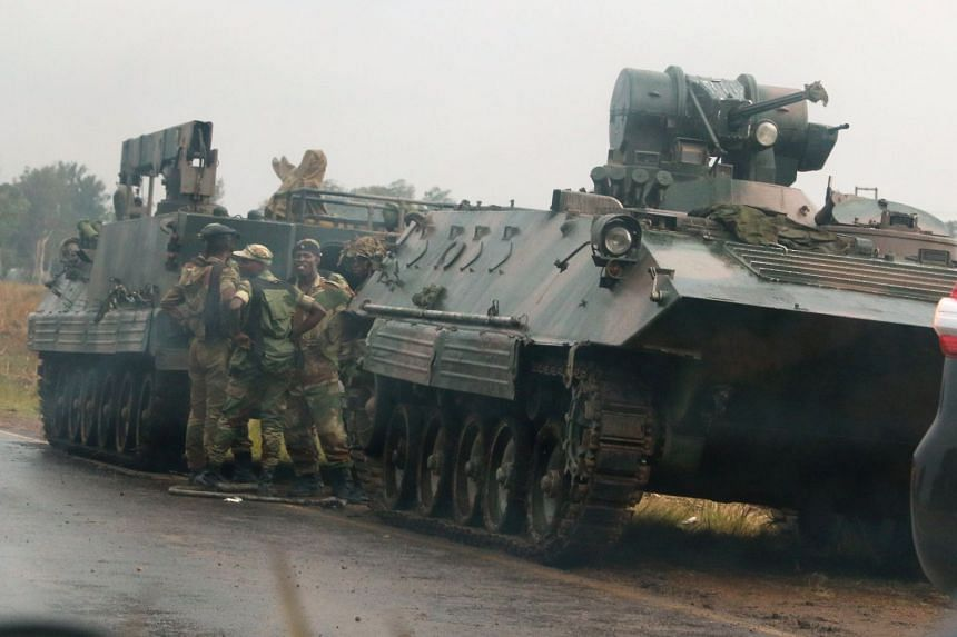 Soldiers stand beside military vehicles just outside Harare, Nov 14,2017.