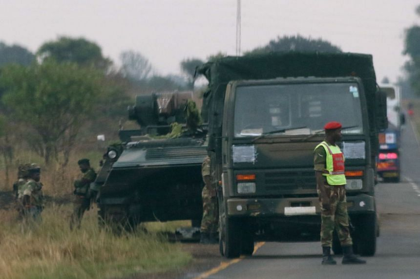 Soldiers stand beside military vehicles just outside Harare, Nov14, 2017.