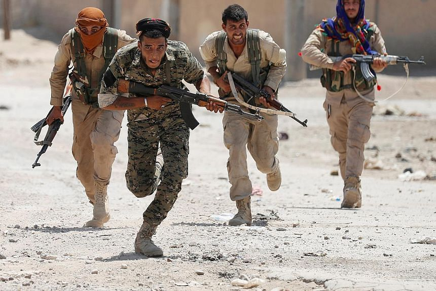 The deal brokered by local officials after four months of fighting in the Syrian city of Raqqa sought to safeguard Syrian Democratic Forces fighters (left) opposed to ISIS, but the arrangement also enabled ISIS militants to leave the city and dispers