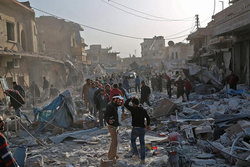 "Syrians searching for survivors amid the debris following air strikes on the rebel-held town of Atareb in Syria's northern Aleppo province on Monday. At least 53 people, including children, were killed despite a ""de-escalation zone"" in place there, t"