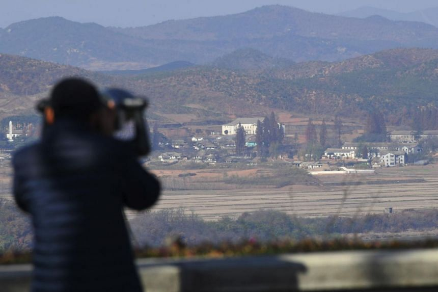 A woman looks through binoculars towards North Korea from a South Korean observation post in Paju near the Demilitarized Zone.