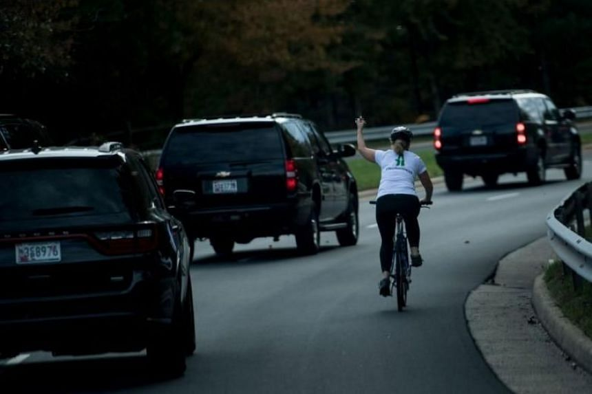 Ms Juli Briskman  gestures with her middle finger as a motorcade with US President Donald Trump departs Trump National Golf Course in Sterling, Virginia on Oct 28, 2017.