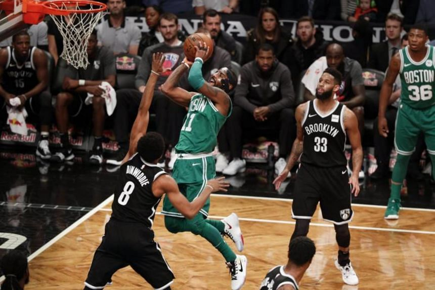 Boston Celtics' Kyrie Irving (centre) drives to the basket as Brooklyn Nets' Spencer Dinwiddie (left) and Allen Crabbe (right) look on during the game between the Boston Celtics and the Brooklyn Nets at the Barclays Center in Brooklyn, New York on No