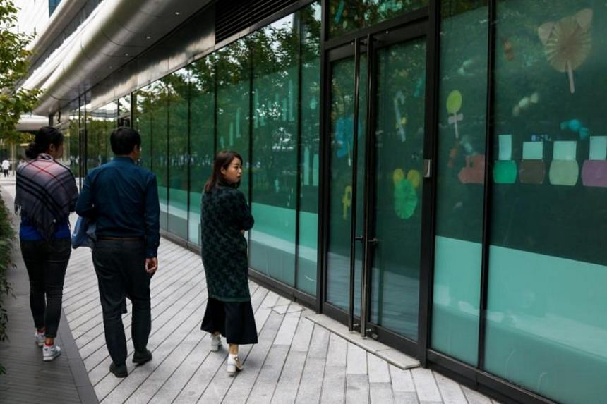 A woman looks at the closed Ctrip day-care centre in Shanghai on Nov 15, 2017. Video footage surfaced last week showing young children of Ctrip employees being roughly handled, and punished by being force-fed what parents claimed was spicy mustard.