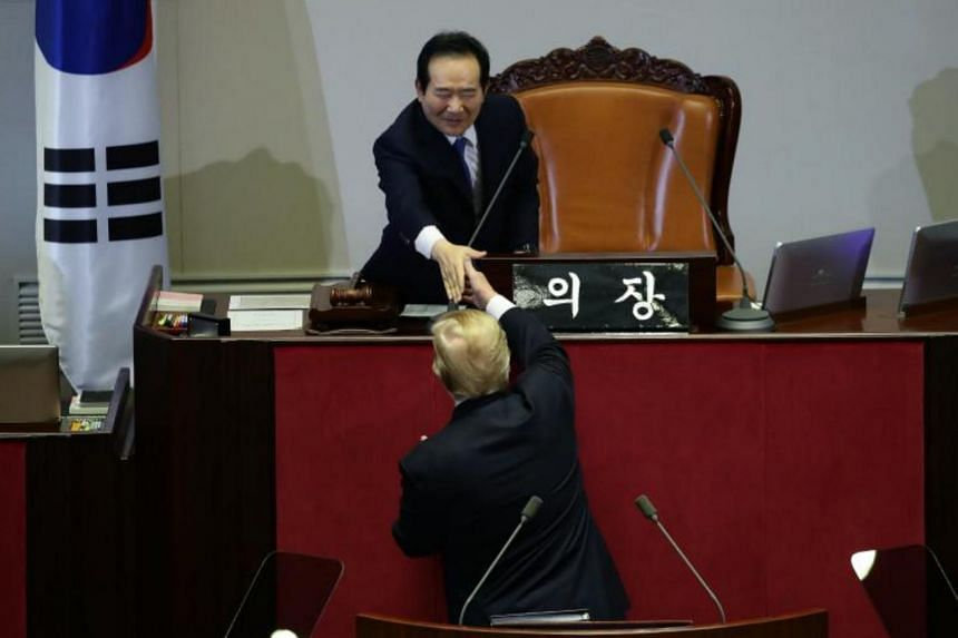 US President Donald Trump shakes hands with speaker of the South Korean National Assembly Chung Sye-Kyun after his speech at the National Assembly in Seoul on Nov 8, 2017.