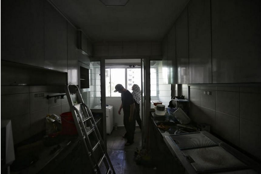 Mr Shah Rizal Abdul Razak, a 34-year-old civil servant, and his wife Haryati Ali, a 31-year-old receptionist, checking the restoration work done in their kitchen and laundry area on Nov 4, 2017.