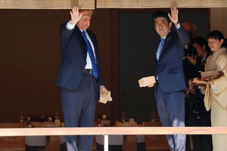 U.S. President Donald Trump and Japan's Prime Minister Shinzo Abe wave after feeding carp before their working lunch at Akasaka Palace in Tokyo, Japan on Nov 6, 2017.