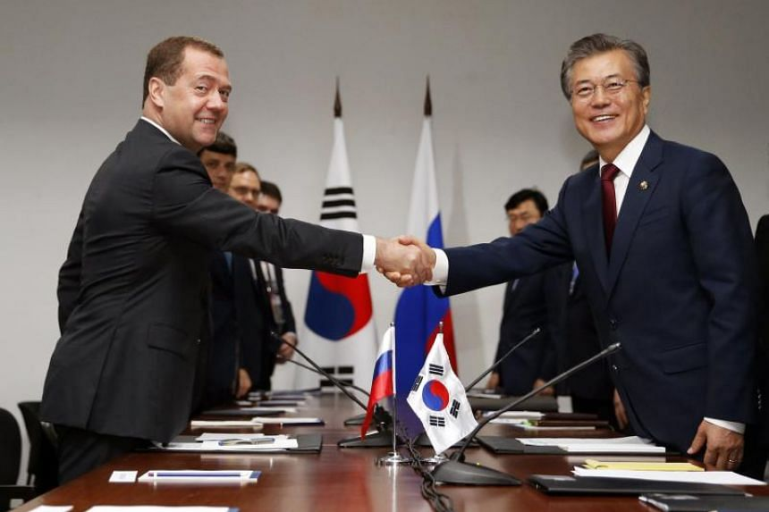Russian Prime Minister Dmitry Medvedev (left) shakes hands with South Korean President Moon Jae In (right) during their meeting on the sidelines of the East Asia Summit in Manila.