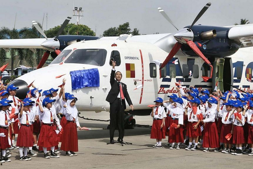 """President Joko """"Jokowi"""" Widodo and dozens of elementary school students fly paper airplanes next to the N219 aircraft that has just been named Nurtanio at Halim Perdanakusuma Airport in Jakarta on Nov 10, 2017."""