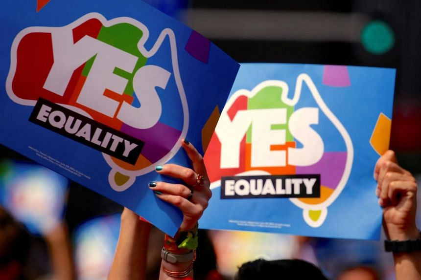 People participating in a march hold aloft posters supporting a 'Yes' vote in a non-binding poll, conducted by post, to inform the government on whether voters want Australia to become the 25th nation to permit same-sex marriage, in central Sydney, A