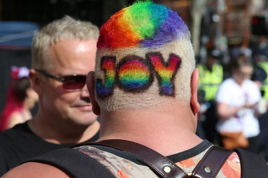 A man with a rainbow color hairstyle is seen as people gathered in front of Melbourne's State Library of Victoria for the outcome of the same-sex marriage vote.