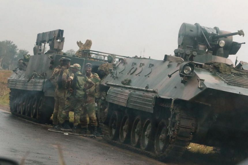 Soldiers stand beside military vehicles just outside Harare, Zimbabwe.