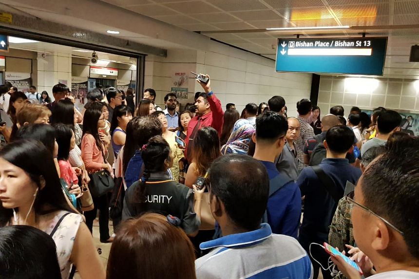 An SMRT staff directs the crowd during the service disruption.