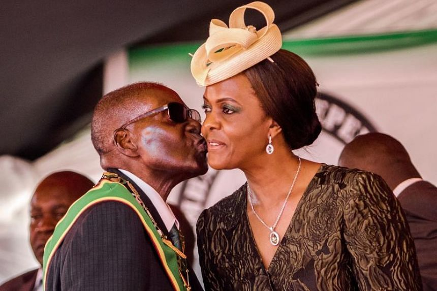 This file photo taken on April 18, 2017, shows President Robert Mugabe kissing his wife and first lady Grace Mugabe during the country's 37th Independence Day celebrations at the National Sports Stadium in Harare.