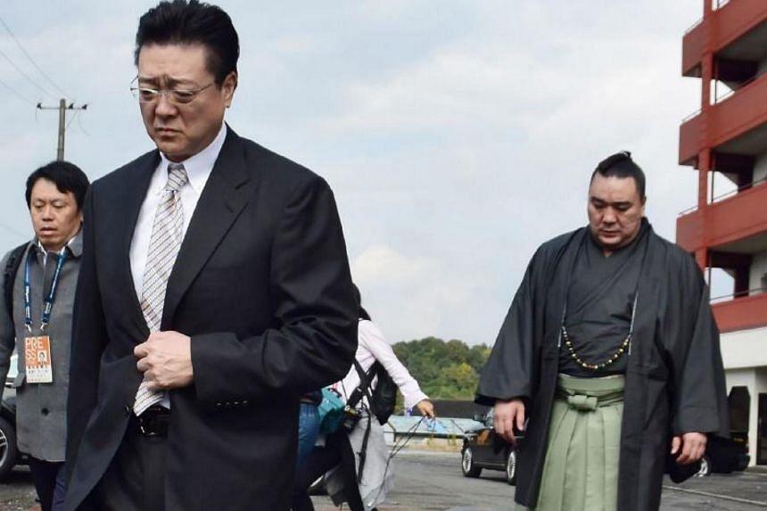 Mongolian sumo wrestler yokozuna Harumafuji (right) and stable master Isegahama on their way to apologise to Mongolian wrestler Takanoiwa Yoshimori, on Nov 14, 2017.