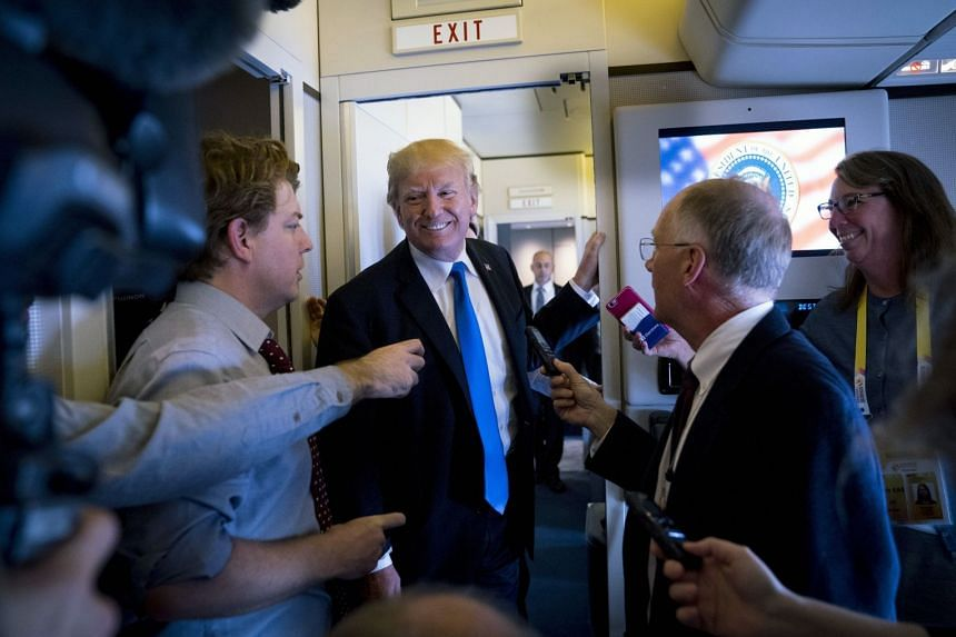 President Donald Trump speaks to reporters aboard Air Force One as the plane departs Manila, Nov 14, 2017.