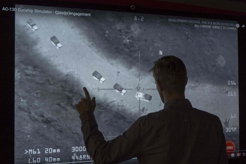 A journalist looks at a YouTube video showing images from an aerial assault video game.
