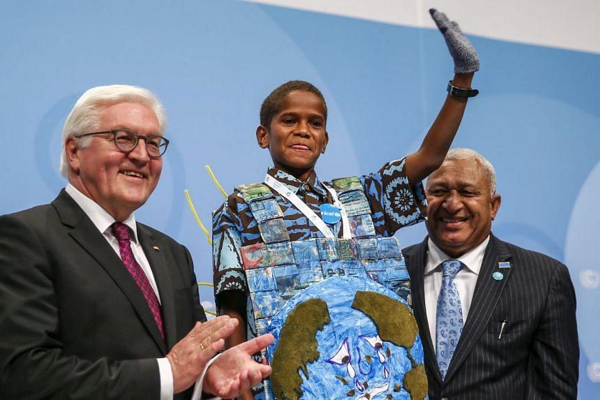 Timothy Naulusala wave after his speech, with German President Frank-Walter Steinmeier (left) and Fiji Prime Minister Frank Bainimarama.