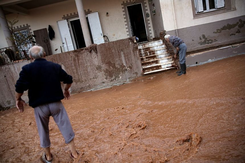A local cleans the mud from the entrance of his house as another crosses a flooded street in Mandra, Greece, Nov 15, 2017.