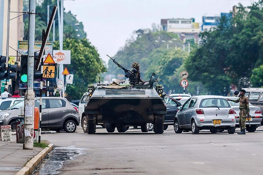 South African President Jacob Zuma said President Mugabe (above) had indicated in a phone conversation that he was fine. An armoured personnel carrier stationed at an intersection in Harare yesterday, as soldiers controlled major intersections near g