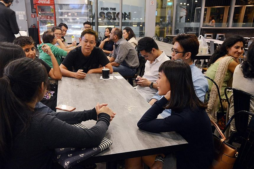 """Participants at the Death Cafe, which drew 20 people, including Ms Carol Lim (right foreground). They discussed questions such as """"what is death like?"""" and shared takeaways and personal experiences. Participants sharing their thoughts on death and li"""
