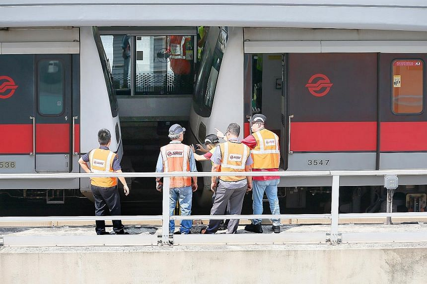 SMRT officials examining the two trains which had collided yesterday morning. The signalling system had mistakenly profiled the stalled vehicle as a three-car train instead of the six-car train that it was. As a result, a second train behind the firs