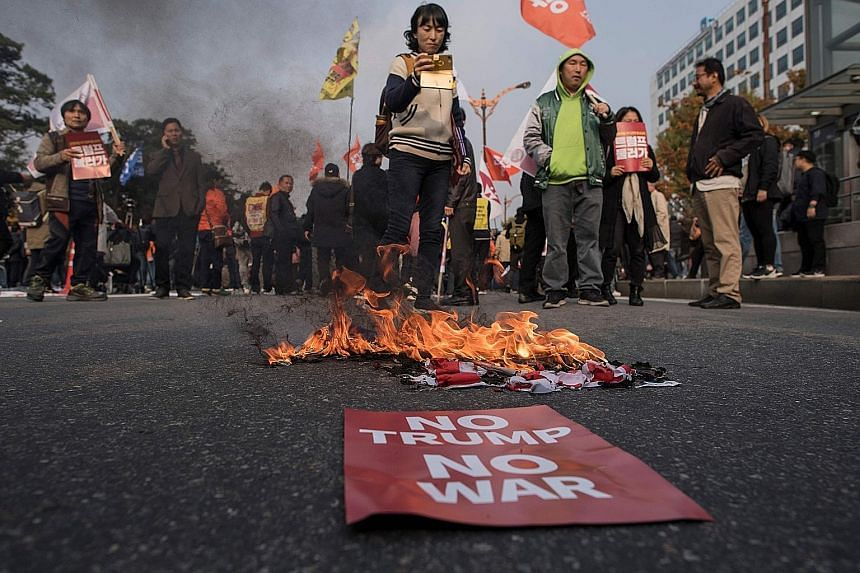 Anti-Trump protesters burning a US flag during a rally outside the National Assembly, where Mr Donald Trump was speaking, in Seoul on Nov 8. Before his visit, there were fears that he would threaten to rain down fire and fury once more on North Korea