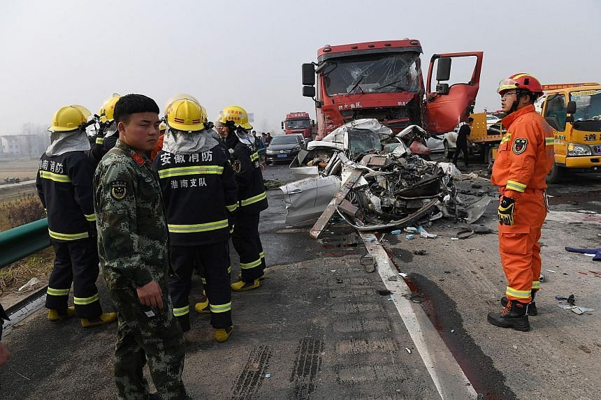Firefighters working at the scene of a major car accident on the highway near Yingshang, Anhui province, in eastern China, yesterday. The pile-up involving at least 30 vehicles killed 18 people yesterday, the local authorities said, leaving dramatic