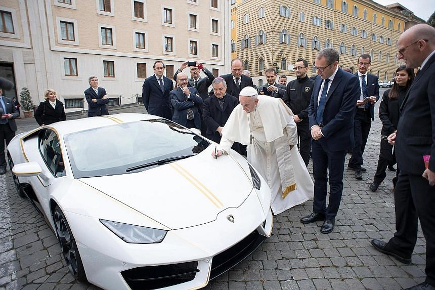 Pope Francis signing a Lamborghini Huracan in front of the pontiff's Santa Marta residence at the Vatican yesterday. Luxury sports-car maker Lamborghini had presented the Pope with a new, special edition papal-themed Huracan. According to the Catholi