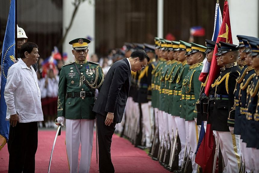Philippine President Rodrigo Duterte accompanying Chinese Premier Li Keqiang as he bows while reviewing an honour guard at the Malacanang presidential palace in Manila yesterday during Mr Li's official visit to the Philippines. Mr Duterte heaped prai